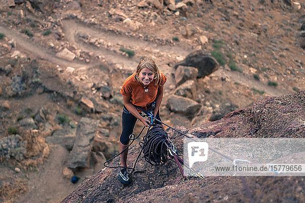 Frau hält Kletterseil und schaut lächelnd nach oben  Smith Rock State Park  Terrebonne  Oregon  Vereinigte Staaten