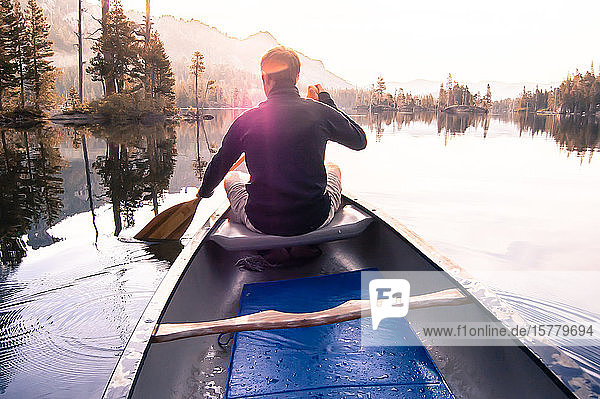 Young man canoeing on Echo Lake  rear view  High Sierras  California  USA