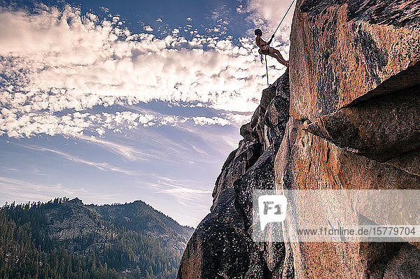 Young male rock climber on rock face  High Sierras  California  USA