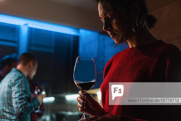 Frau trinkt Wein bei Party in Wohnung
