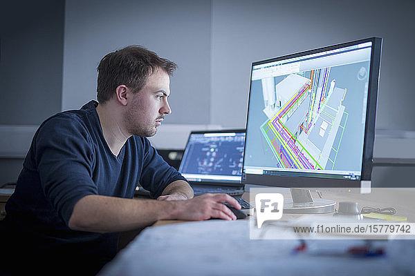 Ingenieur  der CAD-Zeichnungen in einer Metallfabrik prüft.