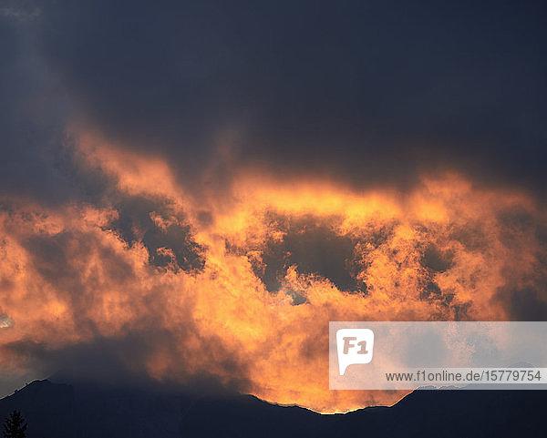 Orangefarbener Sonnenuntergang über den Bergen