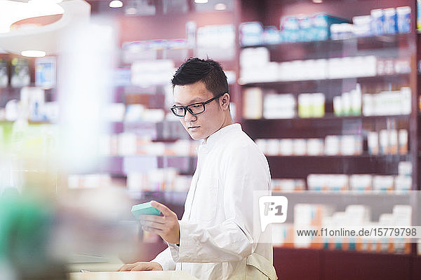 Male Asian pharmacist wearing glasses standing in front of shelves with medicines in a pharmacy.