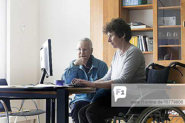 Senior woman and woman in a wheelchair sitting at a table  working on computer.