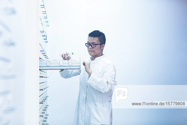 Male Asian pharmacist wearing glasses standing next to a drawer with medicines in pharmacy.