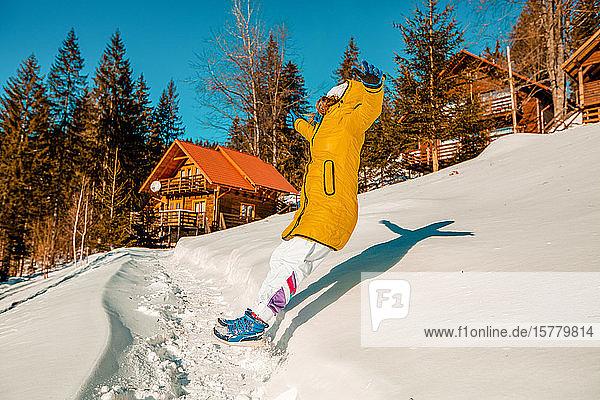 Junge Frau springt rückwärts in den tiefen Schnee in der Nähe einer Hütte.