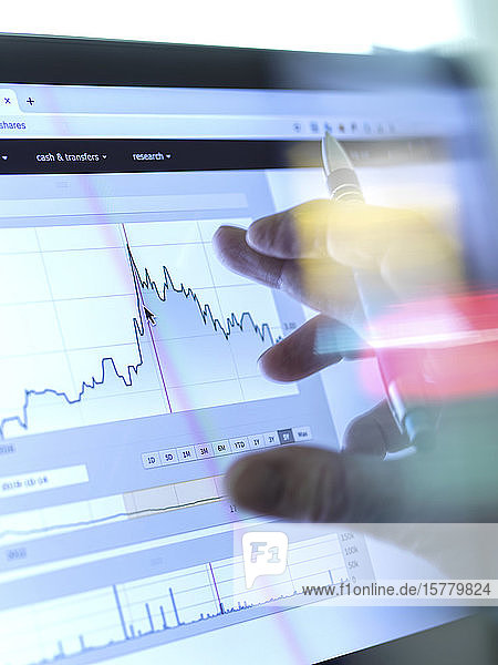 Stock broker analyzing the performance of a company stock on the internet.