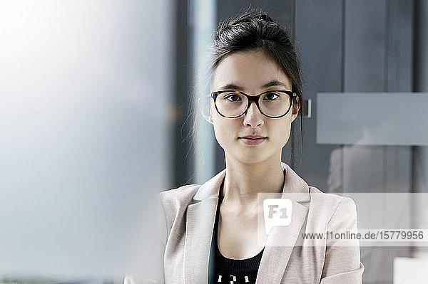 Porträt einer jungen Geschäftsfrau mit dunkelbraunem Haar und Brille.
