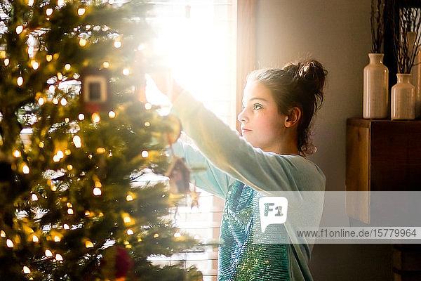 Junges Mädchen schmückt den Weihnachtsbaum zu Hause