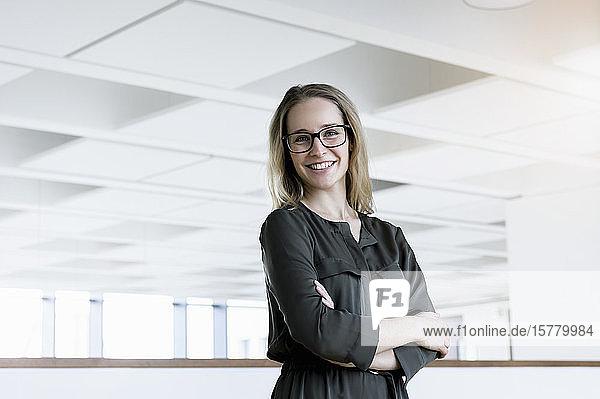 Porträt einer jungen blonden Geschäftsfrau mit Brille.