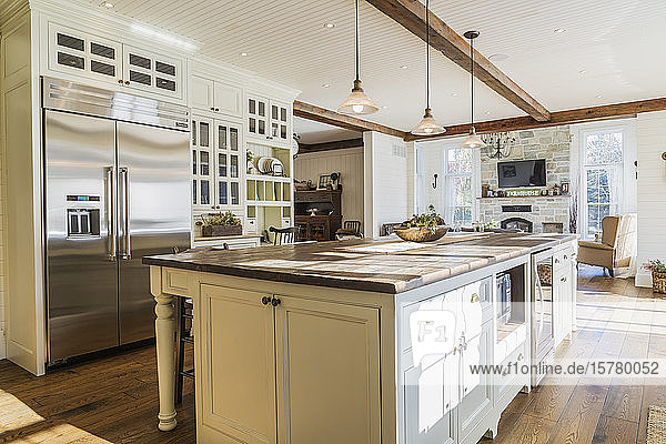 Interior view of country style open plan kitchen with kitchen island and stained oak wood floorboards inside home  Quebec  Canada.