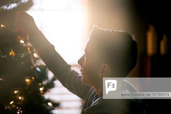 Junge schmückt Weihnachtsbaum zu Hause