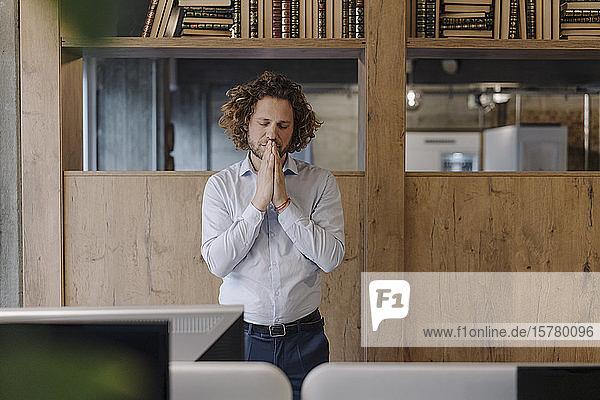 Portrait of serene businessman meditating in office