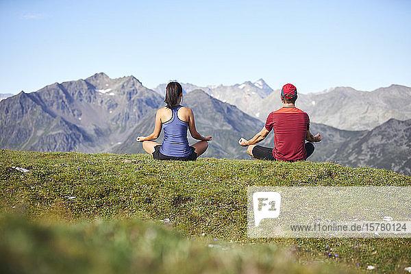 Mann und Frau beim Meditieren in den Bergen  Rückansicht