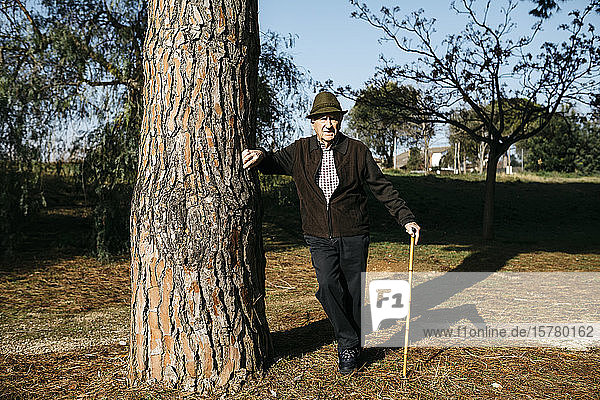 Old man with cane  leaning on tree in park