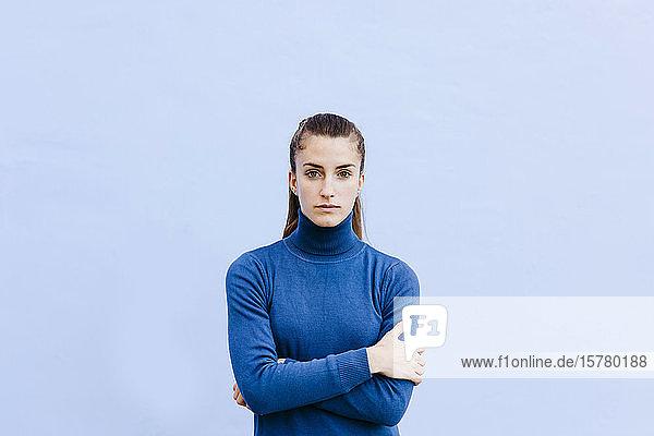 Porträt einer jungen Frau in blauem Rollkragenpullover vor hellblauer Wand