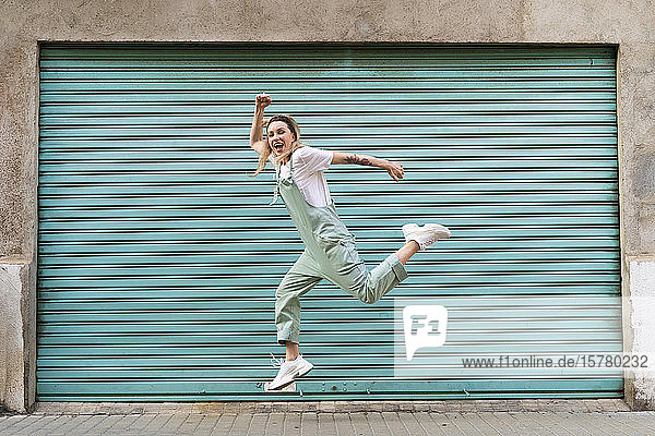 Glückliche junge Frau springt vor Freude in der Stadt