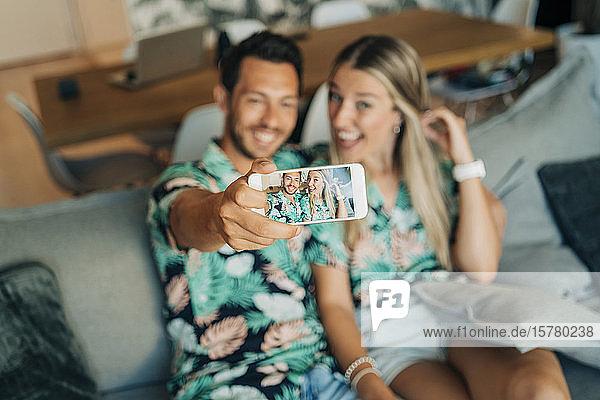 Glückliches Paar sitzt auf der Couch im Wohnzimmer und trägt hawaiianische Hemden und macht einen Selfie