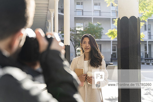 Photographer taking pictureof young woman with book and takeaway coffee