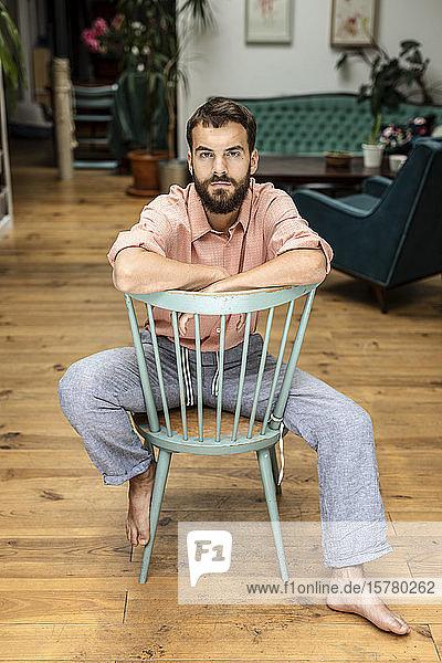 Junger Mann sitzt auf einem Stuhl und schaut in die Kamera