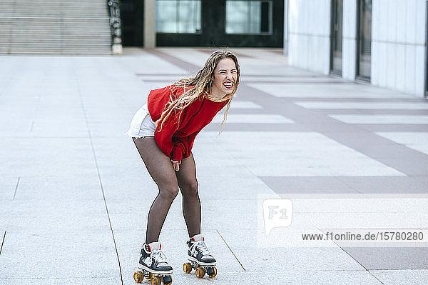 Blonde Frau beim Rollschuhlaufen auf einem Platz