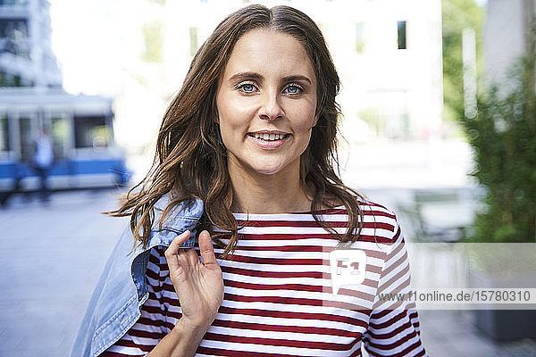 Porträt einer lächelnden brünetten Frau in der Stadt