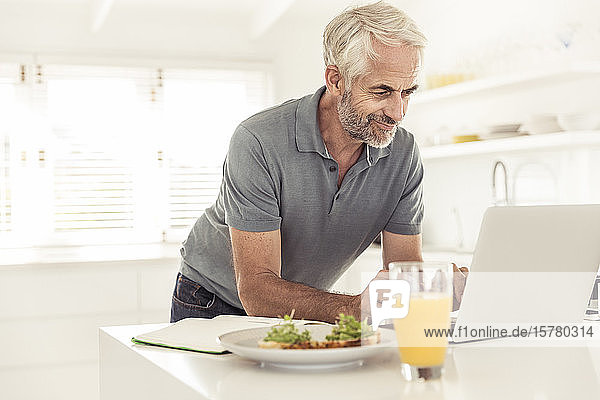 Mature man using laptop in kitchen at home