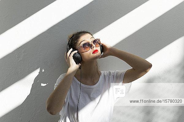 Porträt einer jungen Frau mit roten Lippen  die mit Kopfhörern Musik hört