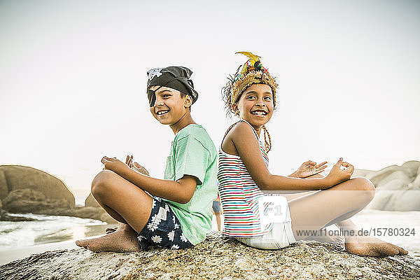Als Piraten und Indianerprinzessin verkleidete Kinder am Strand