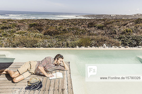 Man lying next to a pool with a notebook