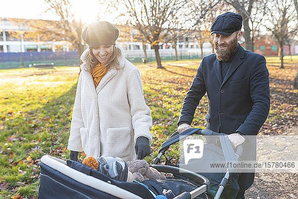 Glückliches Paar mit kleinem Sohn in einem Kinderwagen im Park