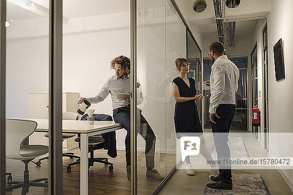 Businessman and businesswoman talking in office with colleague preparing coffee