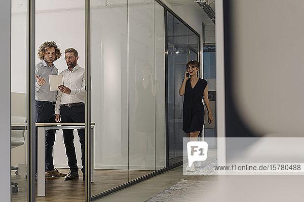 Zwei Geschäftsleute mit Tablett im Büro mit einer Geschäftsfrau am Telefon im Vorbeigehen