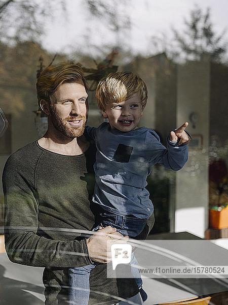 Vater und Sohn schauen zu Hause aus dem Fenster
