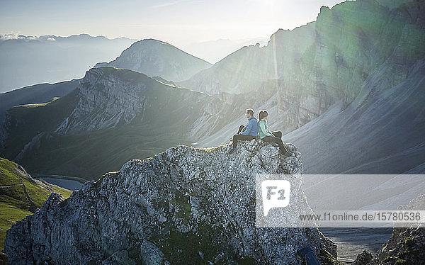 Bergsteiger ruhen sich auf einem Felssporn aus und geniessen die Aussicht  Axamer Lizum  Österreich