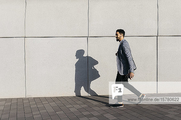 Casual young businessman walking along the wall in the city