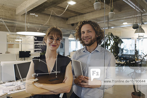 Portrait of confident businessman and businesswoman behind glass pane in office