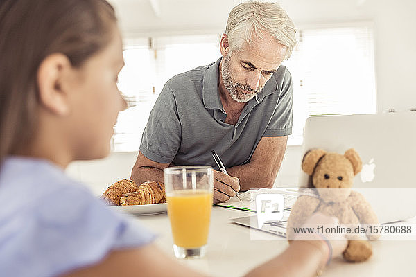 Mature man with daughter working in kitchen at home