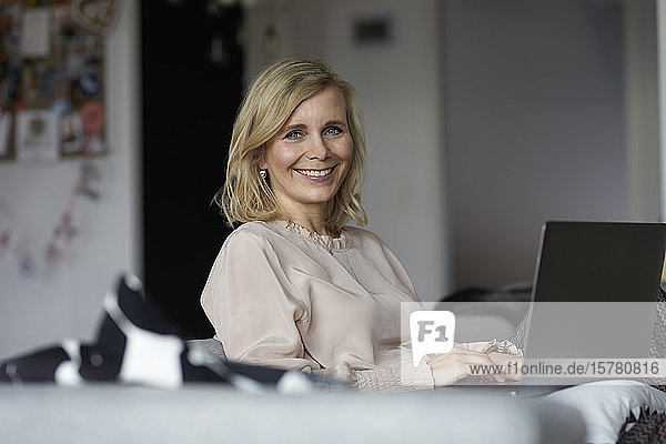 Portrait of smiling blond woman using laptop at home