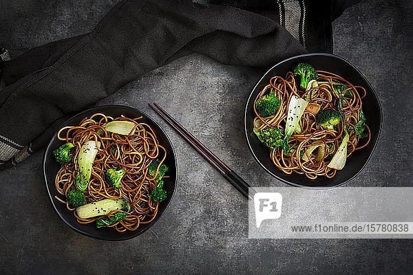Draufsicht auf zwei Schalen Soba-Nudeln mit Pak Choi und Brokkoli  Sojasauce und schwarzem Sesam