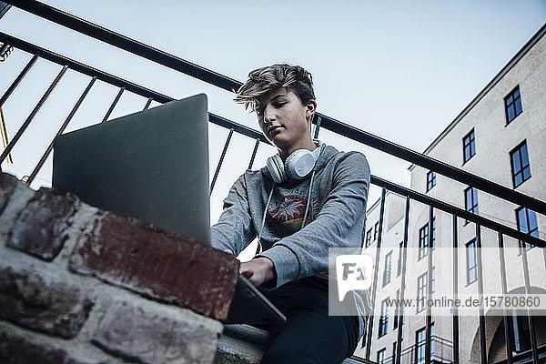 Teenager mit Laptop in der Stadt  Kopfhörer um den Hals