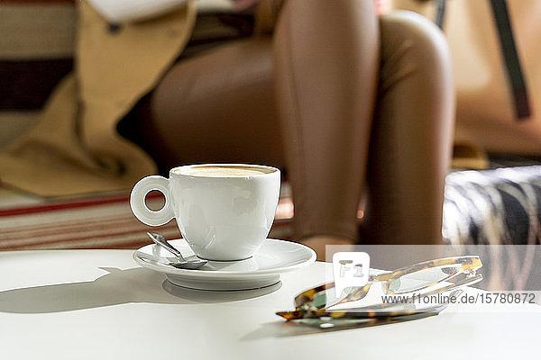 Gläser und Kaffeetasse auf Tisch in einem Café mit Frau im Hintergrund