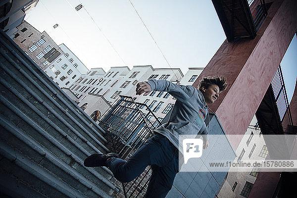 Teenager  der in der Stadt von einer Stufe springt
