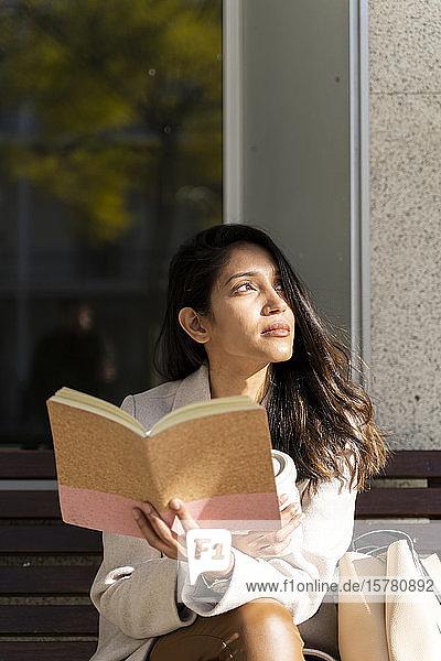 Junge Frau mit Buch auf einer Bank  die zur Seite schaut