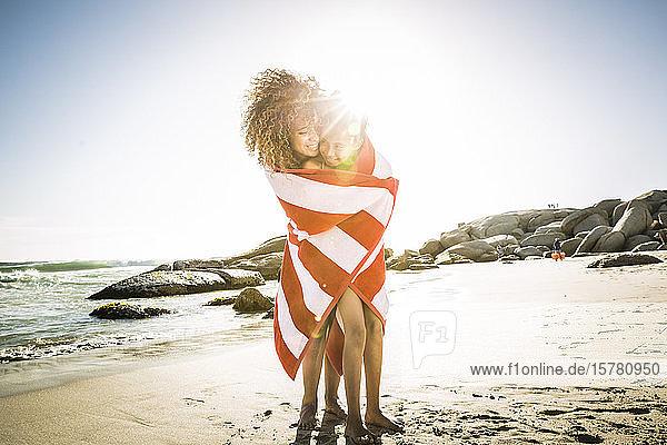 Glückliche Mutter und Tochter eingewickelt in ein Handtuch am Strand Glückliche Mutter und Tochter eingewickelt in ein Handtuch am Strand