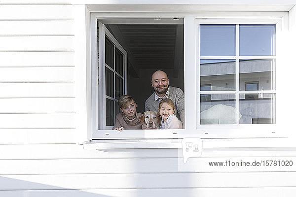 Porträt eines glücklichen Vaters und seiner beiden Kinder  die aus dem Fenster schauen
