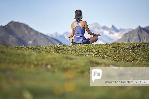 Frau meditiert in den Bergen  Rückansicht