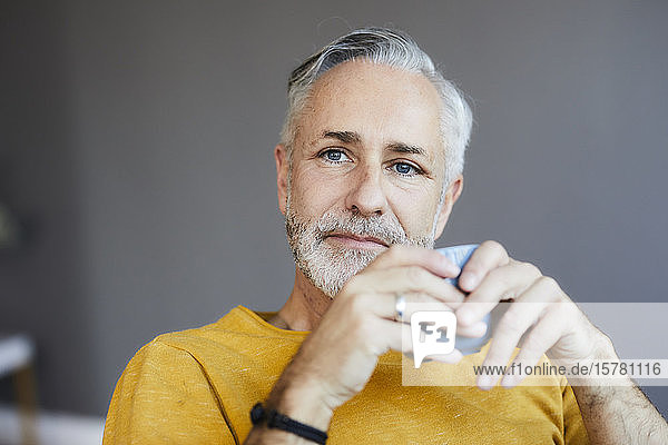 Portrait of relaxed mature man at home with cup of coffee