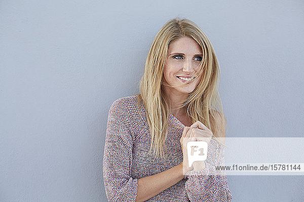 Porträt einer lächelnden blonden jungen Frau mit einem Strickpullover