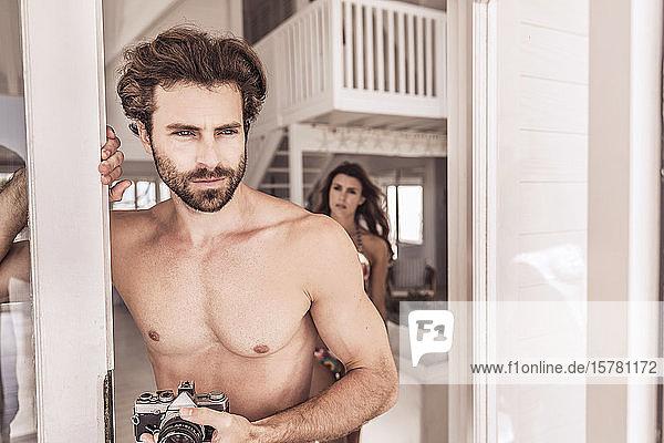 Junger Mann mit Oldtimer-Kamera im Türrahmen stehend